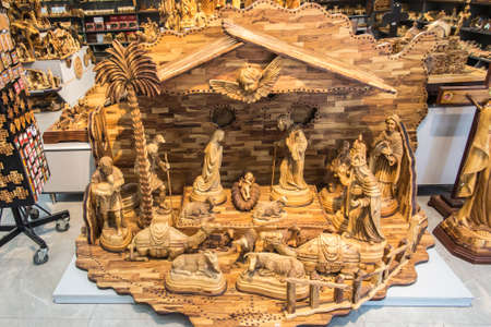 Christmas Nativity Scene of baby Jesus in the manger with Mary and Joseph in silhouette surrounded by animals and the three wise men magi. Olive wood sculptures for sale in Bethlehem