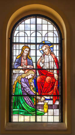 Kalety Miotek, Poland, April 7, 2020: Stained glass window in the church of St. Francis of Assisi in Miotek in Silesia in Poland. The woman washes and anoints Jesus' feet