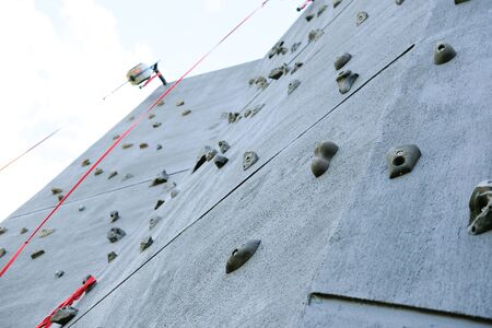 Outdoor climbing wall, an artificially constructed wall with grips for hands and feet.