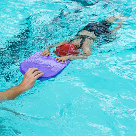 kids learn how to swim in swimming class