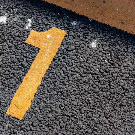 Asphalt parking lot with yellow lot line and yellow lot number 1
