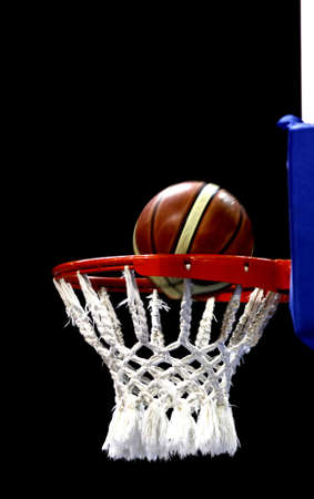 Basketball falling through the net Stock Photo