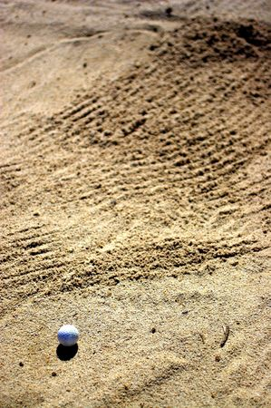 ball of golf in bunker
