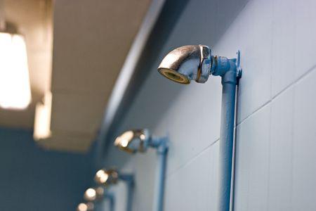 lockers: Gym locker room showers, empty and well lit.