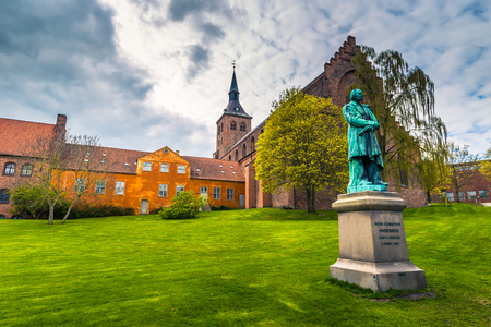 Odense, Denmark - April 29, 2017: Cathedral of Saint Canute and Statue of Hans C Andersen Stock Photo - 78216634