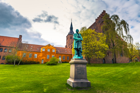 Odense, Denmark - April 29, 2017: Cathedral of Saint Canute and Statue of Hans C Andersen