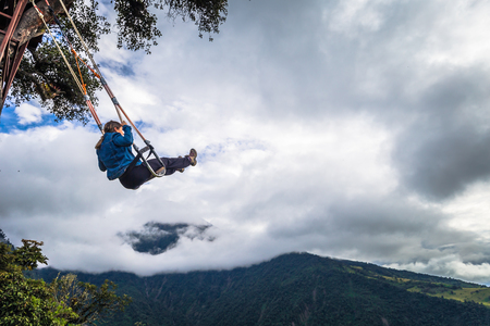 Baños - August 19, 2018: Tourists riding the famous Casa de Arbol End of the World swing in Baños, Ecuador