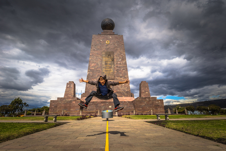 Mitad del Mondo - August 21, 2018: Tourist jumping in the Middle of the World monument in Mitad del Mondo, Ecuador Editorial