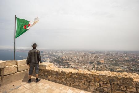 Western traveler by the Algerian flag overlooking the city of Oran, Algeria