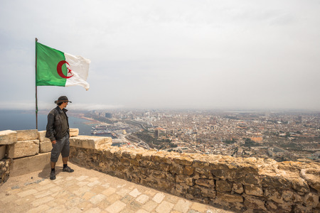 Western traveler by the Algerian flag overlooking the city of Oran, Algeria Stok Fotoğraf - 97683791