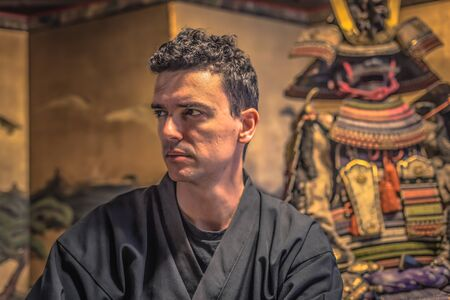 Kyoto - May 29, 2019: Western traveler by the side of a Samurai armor in a Samurai Experience event in Kyoto, Japan Editorial