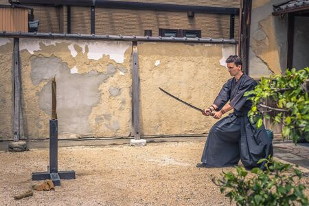 Kyoto - May 29, 2019: Western traveler practicing Iaido sword fighting in a Samurai Experience event in Kyoto, Japan Editorial