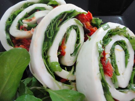 healthy salad buffalo cheese rolls with arugula and sun-dried tomatoes 写真素材