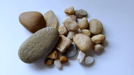 Pile of rocks and pebbles on white background.