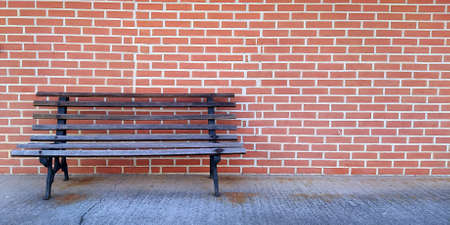 wooden bench against a red brick wall building 写真素材