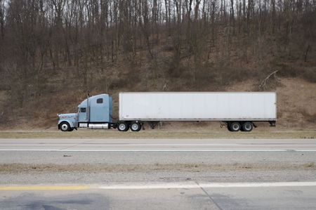 Side Shot of Semi Truck on the Highway with white trailer Stock Photo