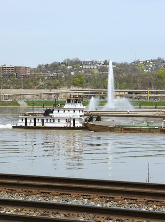 Barge passing by Pittsburghs Point Fountain with Train Tracks in Foreground
