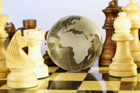 Globe and chess pieces Фото со стока