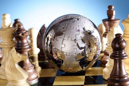 Globe puzzle and chess pieces Фото со стока