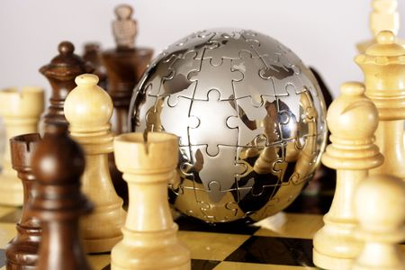 Globe puzzle and chess pieces Stock Photo