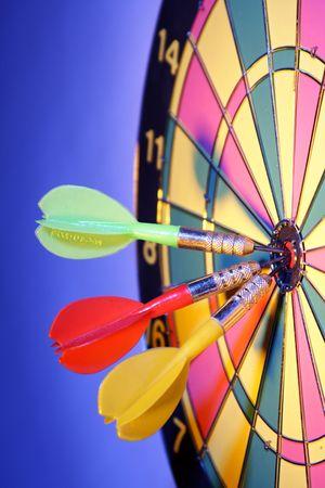 Darts on bulls eye of a dart board photo
