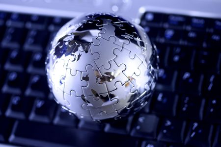 Jigsaw globe puzzle on laptop keyboard