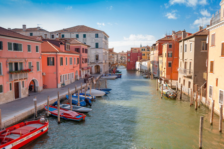 vena: Colorful houses and boats along canal Vena in the venetian center of Chioggia, Veneto, Italy Stock Photo