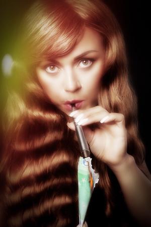 woman lights her vape pen with a burning bank note Stok Fotoğraf