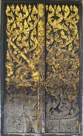 タイの寺院で木製のドアの上の古代の芸術パターン