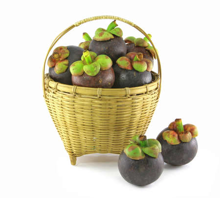 mangosteen in basket on white background, the tropical purple fruit in Thailand photo