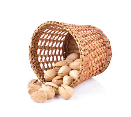 Pistachio nuts in basket on a white background.