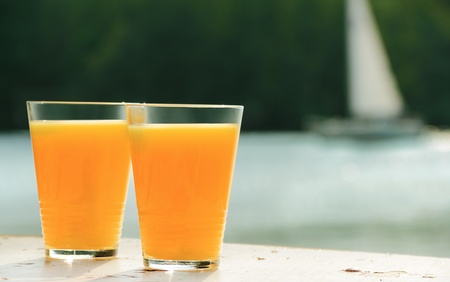 two glasses of orange juice against small sailboat on sea Stock Photo