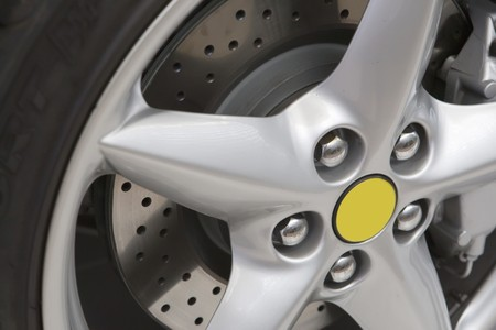 Silver rim with brake disk and black tyre