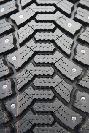 Background of black winter tyre with thorns