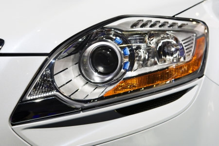 Close up view of headlight white car on black background