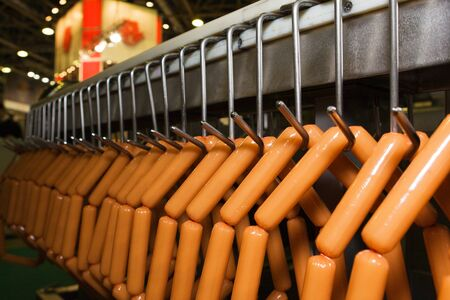 Holder with sausage on conveying machine beltline in food industry Stock Photo