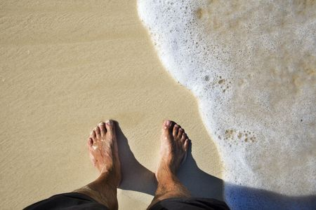 Tanned legs on sand beach in summer