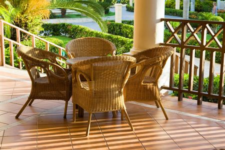 Table and four chairs on patio near bush and grass Stock Photo - 4925545