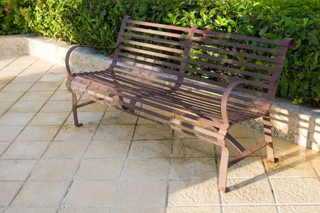 Metall bench on patio near bush and grass Stock Photo - 4959866