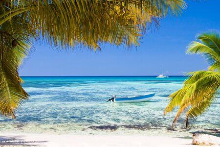 White sand beach boat blue ocean and sky