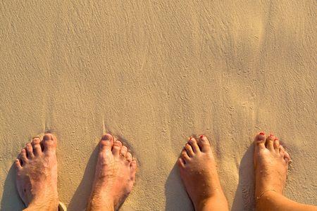 Piernas bronceadas en la playa de arena en el verano de