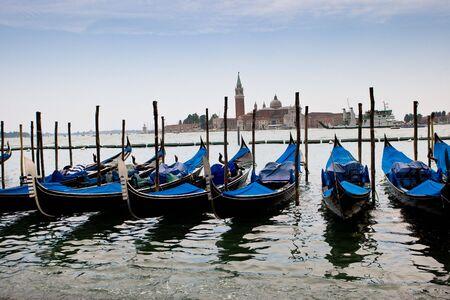 Blue and black gondolas on canal Venezia Italy