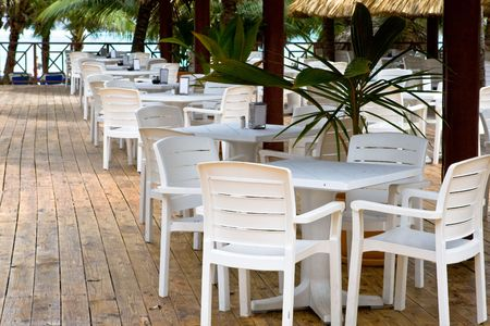 Many white plastic chairs and tables in beach cafe photo