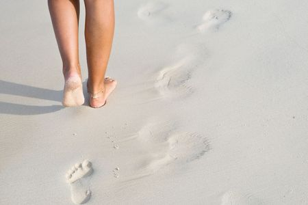 Tanned legs on the beach in ocean