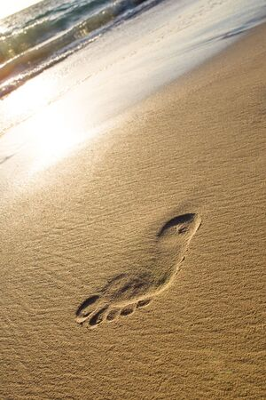 Man foot print on a white sand beach near ocean