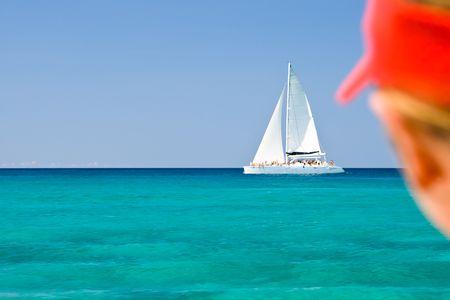 сooking: Boy in a red cap ;ooking on white catamaran in ocean Stock Photo