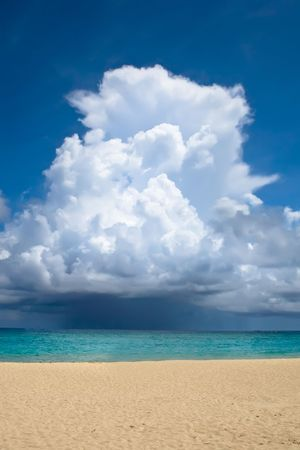 White big cloud over ocean with white sand beach