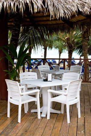 Whie plastic chairs and tables on the patio in the cafe on the beach photo