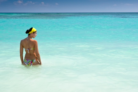 Tanned girls is standing in bright blue ocean under blue sky Stock Photo - 9601820