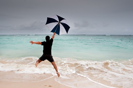 Tanned man jump with umbrella in blue sea under grey cloud sky Stock Photo